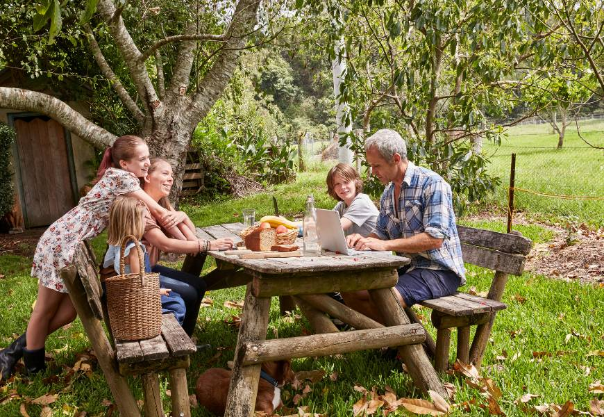 family-at-table-laptop-farm-picnic