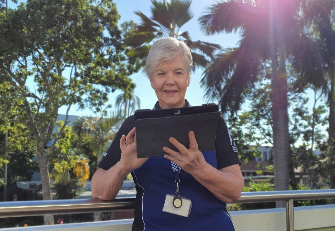 Older female wearing lanyard using tablet device on a balcony with trees in background